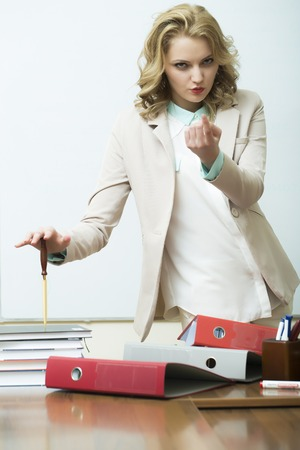 office appliances: Pretty agressive blonde business woman in jacket standing near table with many folders holding knife for cutting paper asking to come looking forward on white background, vertical picture Stock Photo