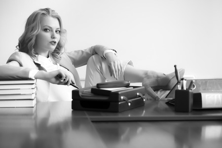 office appliances: Beautiful sexy business woman boss sitting at table with many office appliances looking forward black and white copyspace, horizontal picture Stock Photo