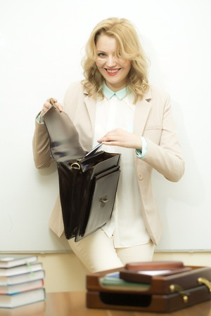 office appliances: Smiling beautiful young business woman with blonde curly hair holding one open black leather briefcase putting documents inside standing near office table on white background, vertical picture