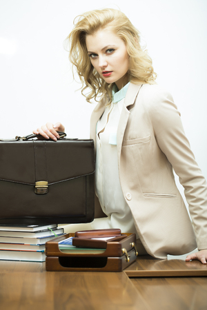 office appliances: Sexual concentrated pretty young business woman with blonde curly hair near black leather briefcase looking forward standing on white background, vertical picture Stock Photo