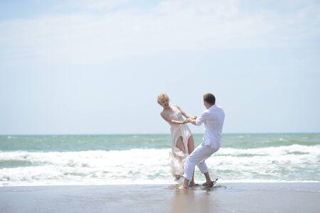 pareja bailando: Atractiva joven pareja feliz pareja de hombre y mujer en el hilado blanco en la costa del océano en la playa de tiempo ventoso día soleado al aire libre en el fondo del cielo azul, horizontal de la imagen Foto de archivo