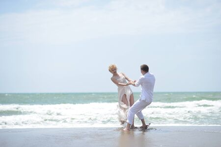 honeymoon couple: Attractive young happy pair couple of man and woman in white spinning on ocean beach coast on windy weather sunny day outdoor on blue sky background, horizontal picture