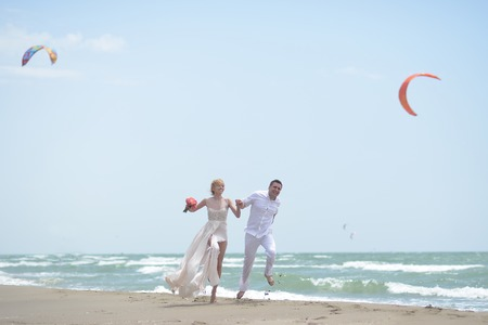 wedding beach: Beautiful laughing young wedding couple of man and woman in white jumping and running along ocean beach shore on windy weather sunny day with paraplanes on blue sky background, horizontal picture Stock Photo