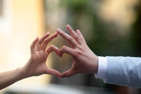 wrist cuffs: Closeup photo of happy married couple making heart with hands and fingers outside, horizontal picture