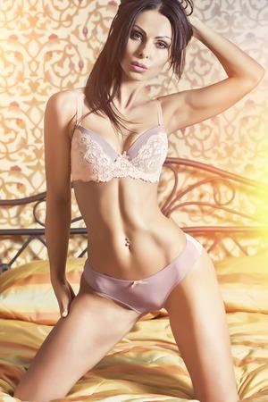 mujer desnuda sentada: mujer morena sexy en violeta del cordón de la ropa interior erótica y lila con cuerpo recto sentada en la cama en el dormitorio mirando hacia adelante en el fondo de la pared con dibujos, imagen vertical