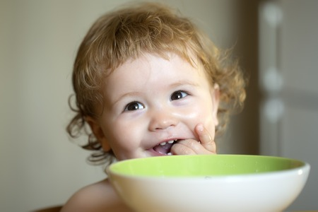 Portrait of sweet little laughing baby boy with blonde curly hair and round cheecks eating from green plate holding spoon and lick fingers closeup, horizontal picture