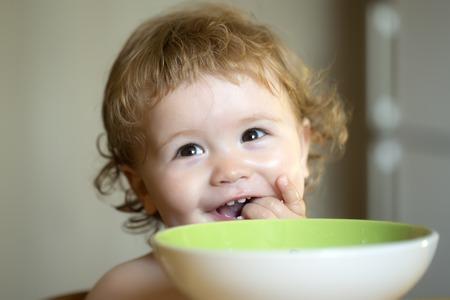 Portret van zoete weinig lachende baby jongen met blond krullend haar en rond cheecks eten uit groene plaat met lepel en likken vingers close-up, horizontaal beeld