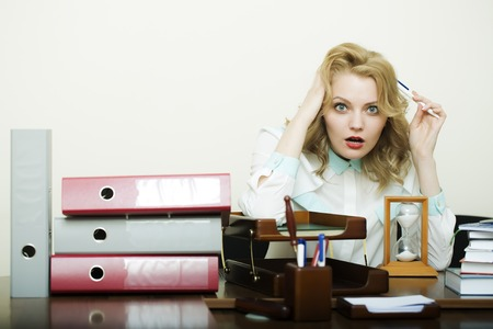 office appliances: Beautiful young secretary woman with blonde curly hair hard working sitting at table with many folders documents and office appliances holding head on white background copyspace, horizontal picture