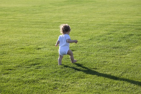 Happy runaway curly barefoot little boy on summer green grass meadow sunny day outdoor, horizontal photo