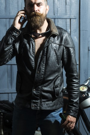 motor cycle: Handsome brutal unshaven sexy male biker in brown leather jacket blue jeans and sun glasses standing in garage near motor cycle holding mobile phone and speaking on wooden background, vertical picture
