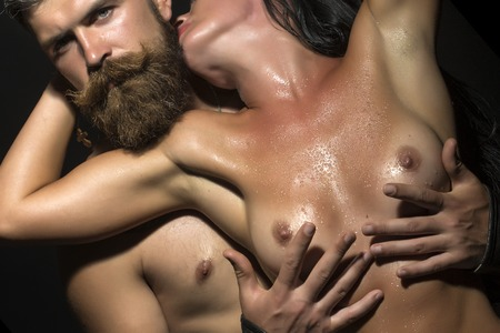 Sexy young sensory couple of undressed unshaven man touching breast of naked woman with beautiful body and soft wet skin embracing guy on black background, horizontal picture