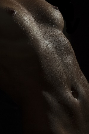 wet breast: Closeup of naked sexual wet female body of young girl in water drops with beautiful breast nipples and flat belly on black background, vertical picture