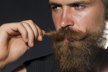 bigote: Retrato de hombre sin afeitar atractiva joven con barba bigote tocar con la mano mirando a otro lado en el fondo negro del estudio, cuadro horizontal