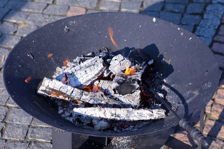smoldering: Closeup photo of round steel brazier with glowing coals and iron poker standing on paved area, horizontal picture