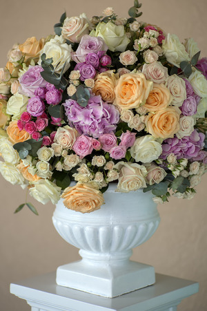 Decoration of wedding bouquet of fresh beautiful flowers of roses and peony white pink violet purple yellow lilac and orange colours in big vase on beige background, vertical picture