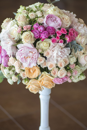nosegay: Decoration of wedding nosegay of fresh beautiful flowers of roses and peony white pink violet purple yellow lilac and orange colours in slim vase indoor, vertical picture