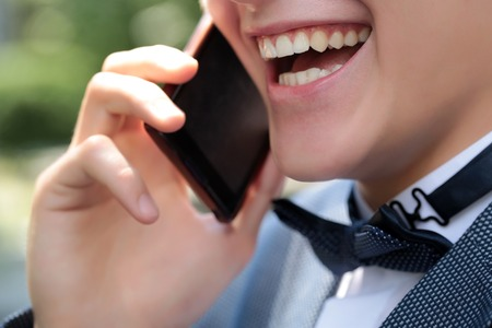 mouth smile: Closeup of healthy clean teeth in open male mouth in pretty smile on young emotional laghing shaven face of boy in black bow tie on white collar holding mobile phone and talking, horizontal photo Stock Photo
