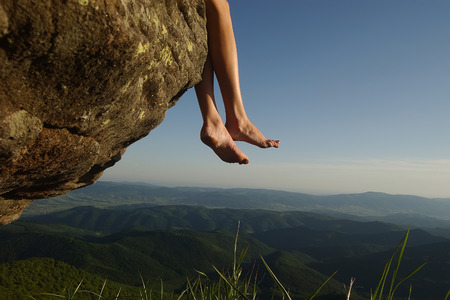 Beautiful landscape view from high mountaing on green hills with wood and human female legs barefoot of girl sitting on rock on natural blue sky copyspace background, horizontal picturepicture Stock Photo