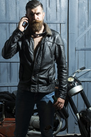 Handsome big unshaven young man with beard and moustache in brown leather biker jacket jeans and sunglasses speaking on cellphone standing near motorcycle on grey wooden background, vertical picture Фото со стока