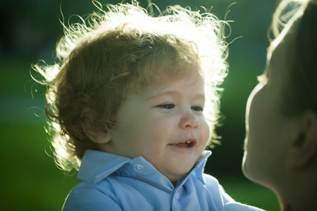 carefully: Portrait of a happy curly baby boy staring at face of his mother carefully with love outdoor closeup, horizontal photo