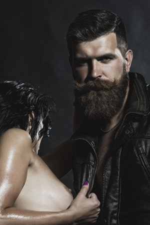 breast nipple: Young couple of brunette naked girl with soft skin and bare breast embracing unshaven man with beard and moustache in leather biker jacket standing on black background, vertical picture