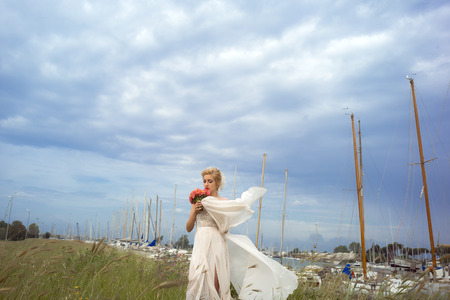 alstromeria: Pensive sensory young bride in wedding dress with train holding coral posy of alstromeria and rose flowers standing on green grass in yacht club berth on cloudy sky background, horizontal picture