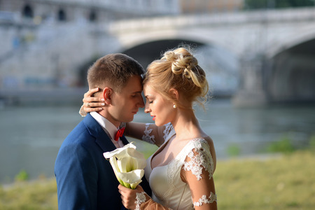 posy: Tender young wedding pair of man in blue jacket and red tie bow embracing girl in white dress with posy of calla flowers standing near river and bridge on sunny outdoor background, horizontal picture Stock Photo