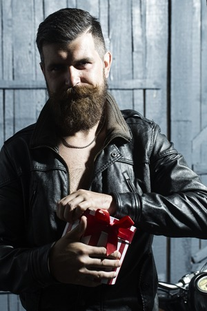 young unshaven: Cool unshaven young boy with beard and moustache in brown leather jacket and chain opening round red white striped gift box with ribbon bow standing on grey wooden background, vertical picture