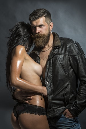 Couple of young undressed woman in panties with soft skin and bare chest embracing unshaven guy with beard in brown leather biker jacket standing on black background, vertical picture