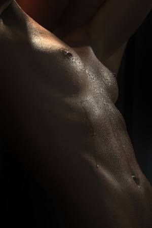 naked belly: Closeup of naked sexual wet female body of young girl in water drops with beautiful breast nipples and flat belly on black background, vertical picture