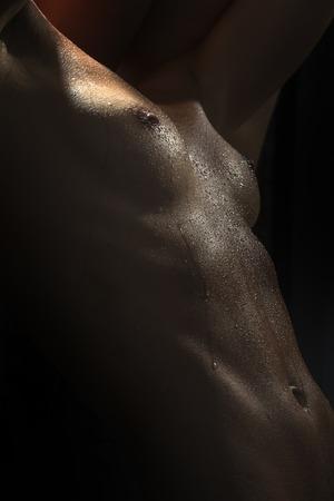 desnuda: Primer de la carrocer�a femenina descubierta mojada sexual de ni�a en gotas de agua con hermosos pezones mamarios y vientre plano sobre fondo negro, imagen vertical,