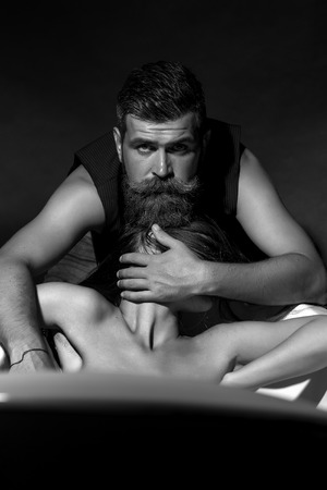 naked girl black hair: Pair of unshaven strong guy with beard and moustache in waistcoat hiding with hand young girl with naked shoulders lying in bathtub black and white, vertical picture