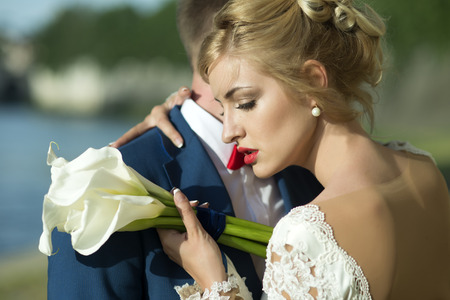blonde couple: Lovely young wedding couple of guy in blue jacket embracing blonde woman in white dress with red lips holding bunch of calla flowers standing on sunny outdoor background, horizontal picture