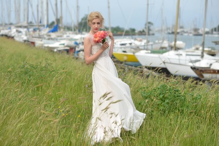 alstromeria: Beautiful sensual young bride in long beige wedding dress with bouquet of alstromeria and rose flowers coral color standing on green grass and spikelet in yacht club berth, horizontal picture