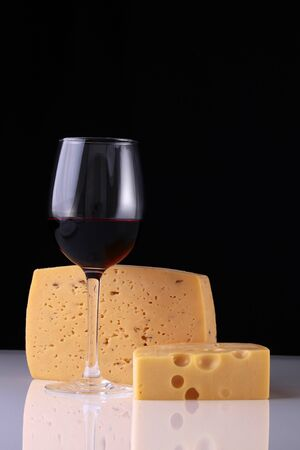 bocal: One glass bocal of red wine standing with two kinds of fresh tasty cheese reflecting on white table top on black studio background copyspace, vertical picture