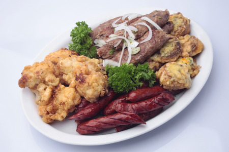 browned: Snack plate of delicious grilled browned sausages with shish kebabs decorated roasted mushrooms stuffed with cheese fried cauliflower and parsley isolated on white, horizontal picture