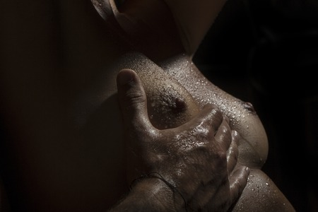 wet breast: Closeup of pretty sexy bare female breast with soft wet skin and nipples of young woman touched by male hand in sexual affection on black background, horizontal picture