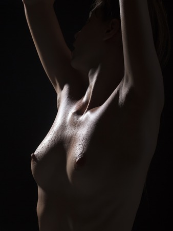 wet breast: One bare young sexy girl with beautiful breast nipples and straight wet body standing with raised hands in passion on black background closeup, vertical picture