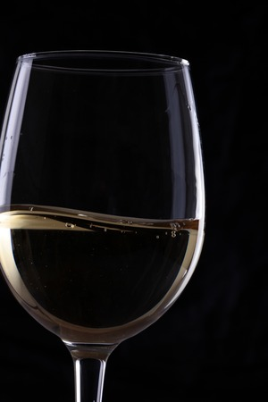 Closeup of one transparent clear elegant glass bocal with white grape rough wine with bubbles in studio isolater on black background, vertical picture