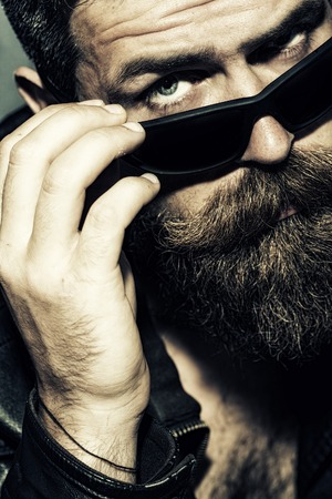 brutal: Portrait of beautiful brutal unshaved male biker with long beard and moustache touching black sunglasses with hand looking forward closeup, vertical picture