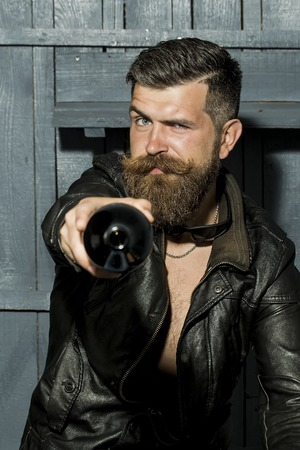 long hair boy: Handsome cool brutal male biker with long beard and moustache in brown leather jacket with open chest holding empty wine bottle looking forward sitting on grey wooden background, vertical picture