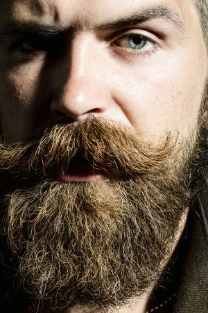 Portret van de sombere brutale ongeschoren man met een lange baard en hendlebar vooruit met getotene wenkbrauwen close-up van mannelijk gezicht, verticaal beeld