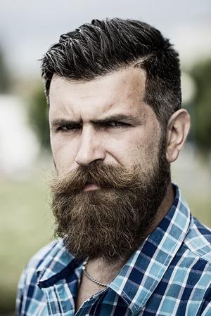 poses de modelos: Retrato de hombre sin afeitar serio guapo con larga barba y bigote hendlebar en camisa blanco y azul claro a cuadros con ganas de pie al aire libre foto, vertical