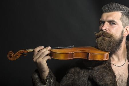 bigote: Hombre sin afeitar brutal musical con larga barba y bigote hendlebar en abrigo de piel marrón con collar y cadena en el pecho sosteniendo el violín de madera en pie en el fondo negro copyspace, horizontal de la imagen