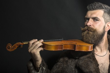 Musical brutal unshaven man with long beard and hendlebar moustache in brown fur coat with collar and chain on chest holding wooden violin standing on black background copyspace, horizontal picture