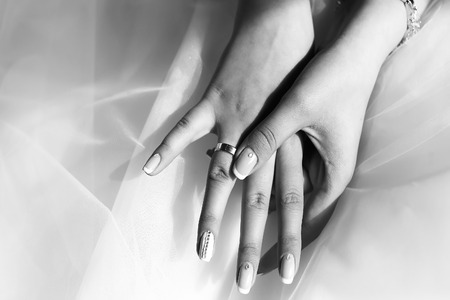 Closeup of female hands with beautiful wedding ring from precious metal on viel fabric of bride dress black and white, horizontal picture Stock Photo