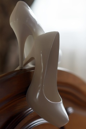 banisters: Closeup of elegant high heeled white laked glossy glamour wedding shoes on wooden banisters of bed in room, vertical picture