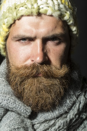 morose: Portrait of morose unshaven homeless man with long beard and hendlebar moustache in knitted yellow hat and grey scarf looking forward standing on black background closeup, vertical picture