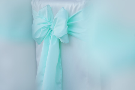 pastel shades: Closeup of decorative light blue bow tie ribbon of soft veil fabric in pastel shades with white color copyspace, horizontal picture Stock Photo