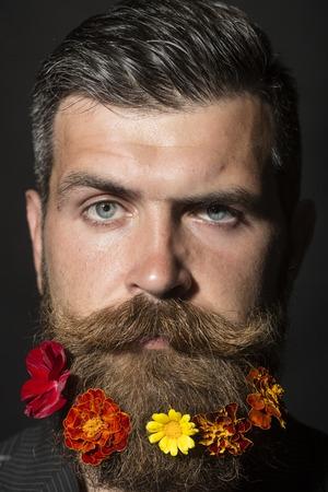 bigote: Retrato del hombre sin afeitar hermoso con larga barba y el bigote arriate hendlebar con las maravillas de colores flores de color rojo y amarillo mirando hacia adelante sobre fondo negro, imagen vertical de color naranja